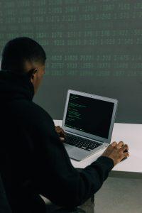 Student wearing hood types on MacBook Air